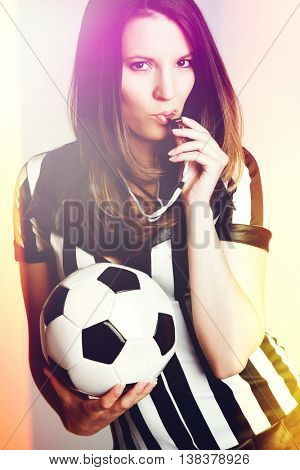 Sexy soccer referee girl blowing whistle
