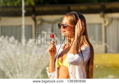 Girl enjoying music with headphones. The girl in sunglasses and a white shirt. She licks a lollipop. Close-up portrait
