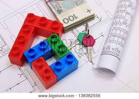 House of colorful building blocks home keys banknotes and electrical diagrams lying on construction drawing of house concept of building house