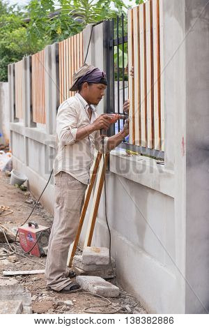 Carpenter Hands Using Electric Drill On Fence Wood