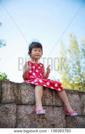 Happy asian girl with thump up and looking at camera at park. Child relaxing outdoors in the day time travel on vacation. Positive human emotion.