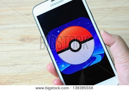 KOTA KINABALU MALAYSIA - 14 JULY 2016: Hands holding a smart phone with screen Pokemon Go logo a free-to-play augmented reality mobile game developed by Niantic for iOS and Android devices.