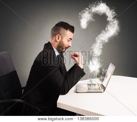 Businessman with puzzled expression looks at his damaged computer