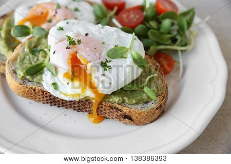 Poached Eggs With Avocado,tomato And Sunflower Sprout On Sourdough Toasts
