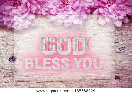 pink flowers on wooden with word GOD BLESS YOU