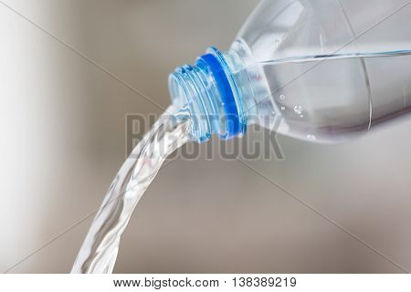 drinking, healthy eating and food storage concept - close up of water pouring from plastic bottle
