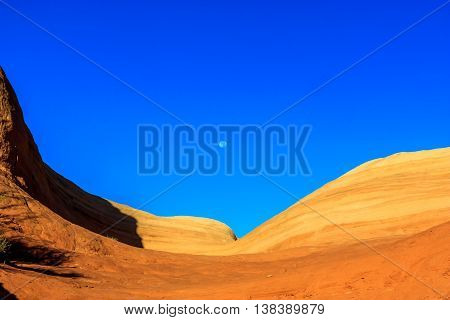 The moon in a blue sky over a wave rock formation in Utah