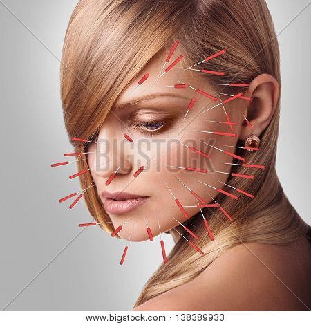 Close-up of performing acupuncture therapy on face over gray background