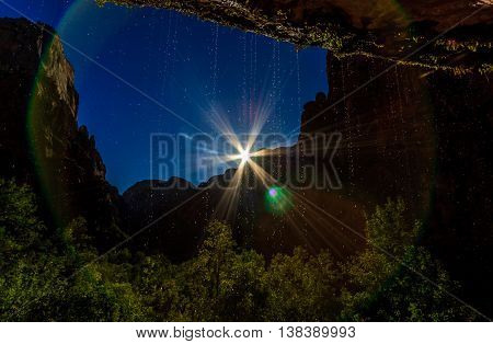 Looking through a dripping spring at the sun in Zion national Park
