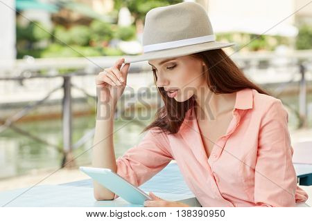 beautiful woman using tablet on lunch break in the street cafe