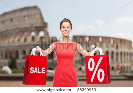 sale, discount, tourism and holidays concept - smiling young woman in red dress with shopping bags with percent sign over coliseum background