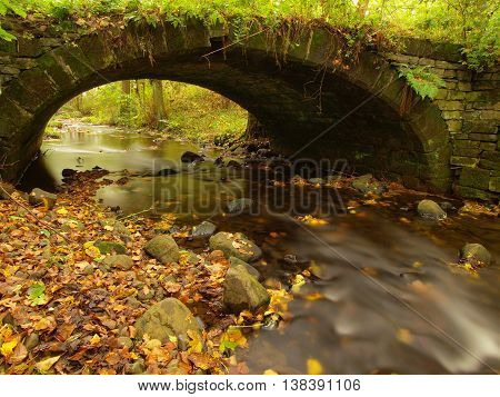 Old stony bridge above autumn river. Water of stream full of colorful leaves, leaves on gravel, blue blurred water.