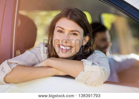 Portrait of beautiful woman looking out from car window on a sunny day