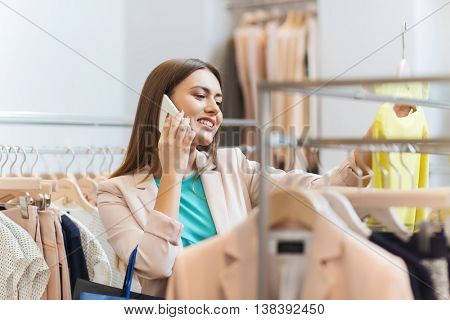 sale, consumerism, fashion, communication and people concept - happy young woman with shopping bags choosing clothes and calling on smartphone in mall or clothing store