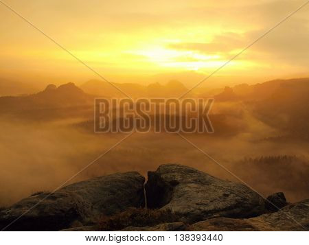 Red daybreak. Misty daybreak in a beautiful hills. Peaks of hills are sticking out from foggy background, the fog is red and orange due to Sun rays.