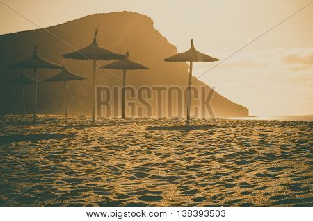 Thatch palapa umbrellas against sunlight at beach Playa la Tejita Montana roja on background. Tenerife island Spain. Retro toned image