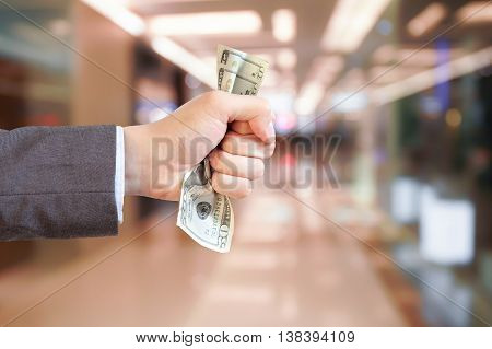 Businessman grasping and giving money in shopping mall blurred background.