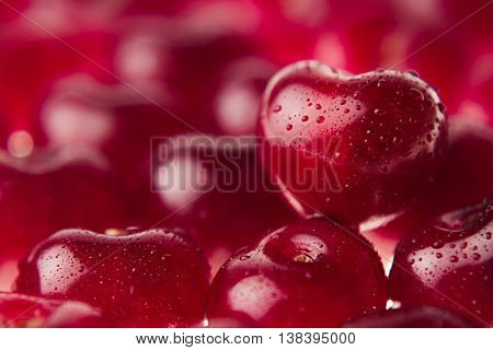 Cherry background with cherry in form of heart. Ripe fresh rich cherries with drops of water. Macro. Texture. Fruit background. Valentine's Day.