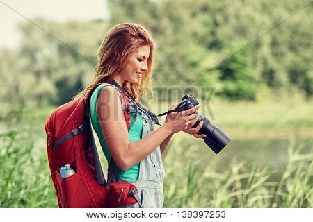 adventure, travel, tourism, hike and people concept - happy young woman with backpack and camera photographing outdoors