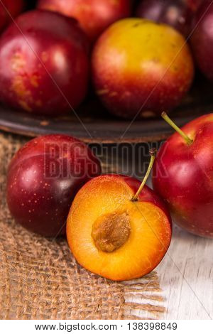 Ripe red plums on old wooden background, selective focus