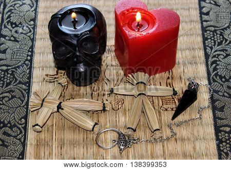 Black magic ritual with mysterious occult and esoteric symbols, objects. Black burning  skull and heart candles,  pendulum with chain and two magic straw voodoo dolls