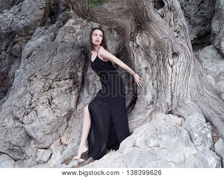 Outdoors fashion photo of beautiful young woman at the mighty ancient tree