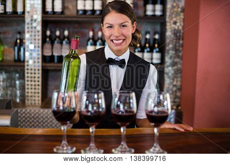 Four glasses of red wine ready to serve on bar counter while bartender holding a bottle in background