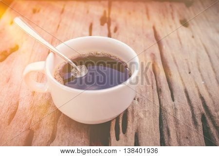 Hot Coffee On Old Wooden Background With Sunlight. Vintage Picture Style.