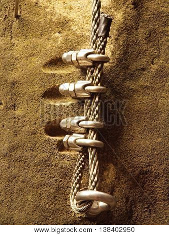 Detail of steel anchor eye and rope end anchored into sandstone rock. Iron twisted rope fixed in block by screws snap hooks.  Trekking via ferrta.