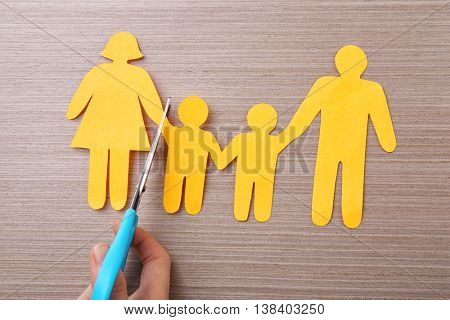 Scissors and paper family on wooden table. Family law concept