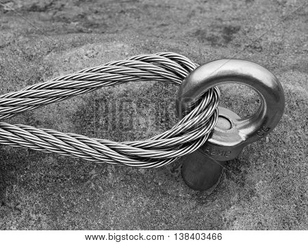 Detail of steel anchor eye and rope end anchored into sandstone rock. Iron twisted rope fixed in block by screws snap hooks.