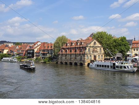 BAMBERG GERMANY - MAY 18 2015: View of old buildings on the left bank of the Regnitz river. Tourists on a passenger ship. Historic city center of Bamberg is a listed UNESCO world heritage site