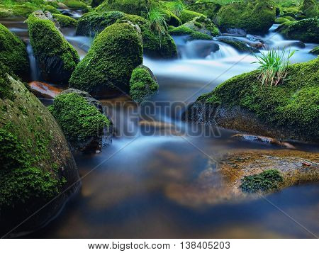 Mossy boulders in curved mountain river. Broken trunk on blocked at stream bank above bright blurred waves of clear water.