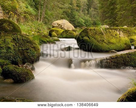 Mountain river with blurred curves in rapids between mossy boulders and bubbles create trails on level.