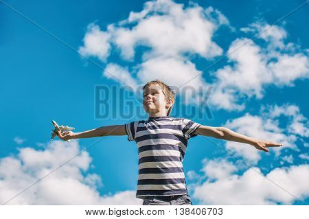 boy plays the pilot of the aircraft. boy holding a toy passenger plane and spread his arms wide for a flight on a background of blue sky