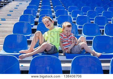 cheerful boys laughing at sports tribune. two cute boys sitting on an empty grandstand stadium and having fun