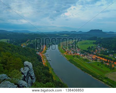 Early morning above the river at beautiful park Saxony Switzerland. Peaks of hills increased from foggy background, the mist is increasing from river.