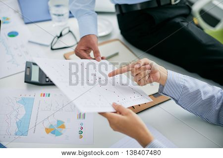Hands of financial managers pointing at document