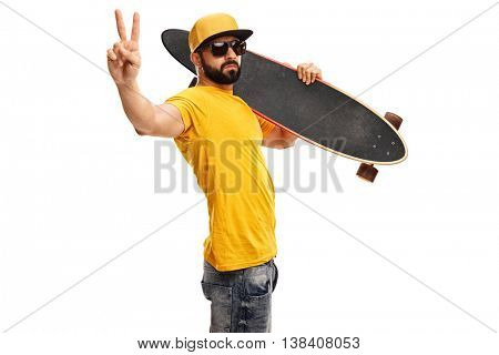 Cool skater guy holding a longboard and making a peace sign with his hand isolated on white background