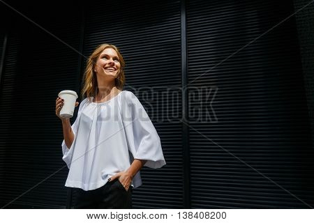 Portrait of young smiling girl holding disposable coffee cup on dark wall background