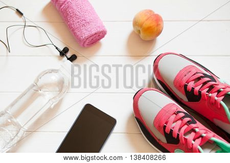 Red Sneakers With Towel, Peach, Bottle With Water, Smartphone With Headphones On White Wooden Backgr