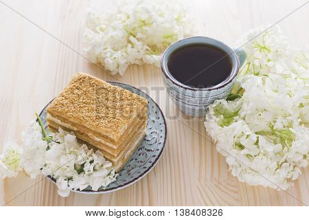 Napoleon cake cup of coffee and white hydrangea on wooden table