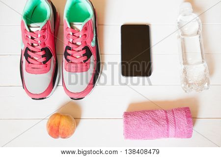 Red Sneakers With Towel, Peach, Bottle With Water, Smartphone On White Wooden Background Indoors. Sp