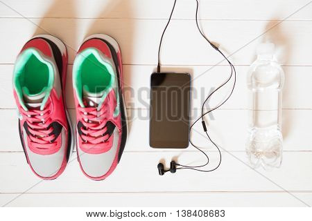 Red Sneakers Bottle With Water, Smartphone With Headphones On White Wooden Background Indoors. Sport