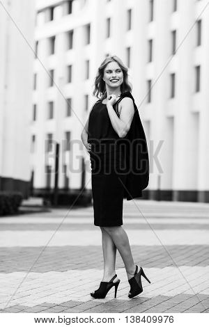 Black-and white portrait of business woman outside office buildings. Full body portrait