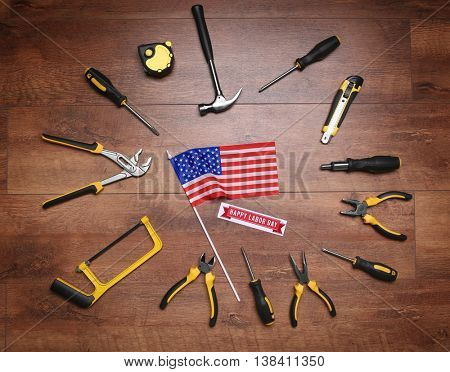 Tools and American flag on a wooden background. Labor day concept