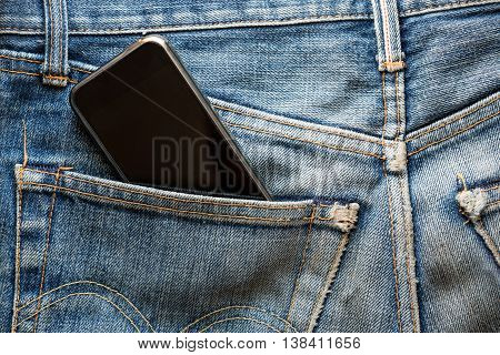 Mobile phone in back pocket faded jeans