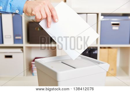 Hand with ballot paper and election booth in polling station