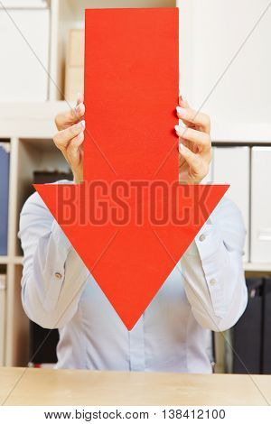 Big red arrow pointing down in an office being held by hands