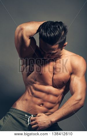 handsome young macho man with muscular sexy body and six packs on torso in pants in studio on grey background